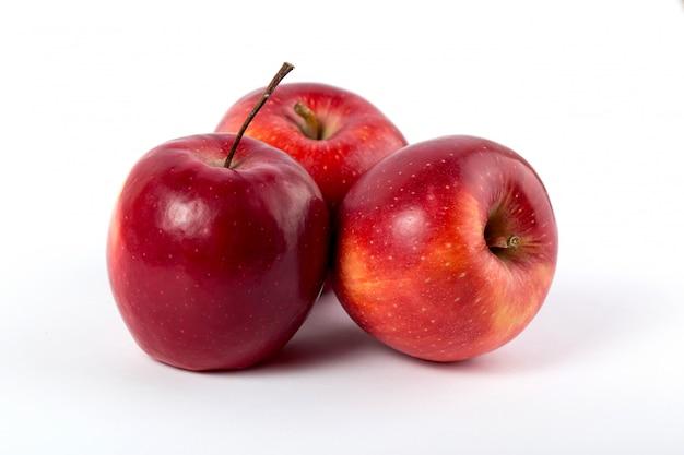 Manzanas rojas frescas suaves jugosas enteras perfectas en el escritorio blanco