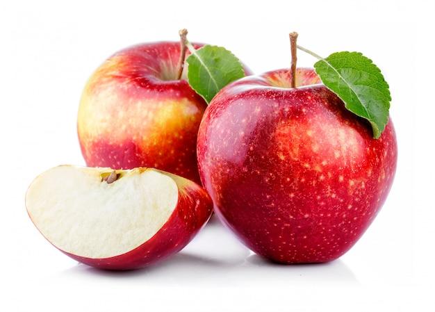 Manzanas rojas con hojas y rodajas aisladas sobre un blanco