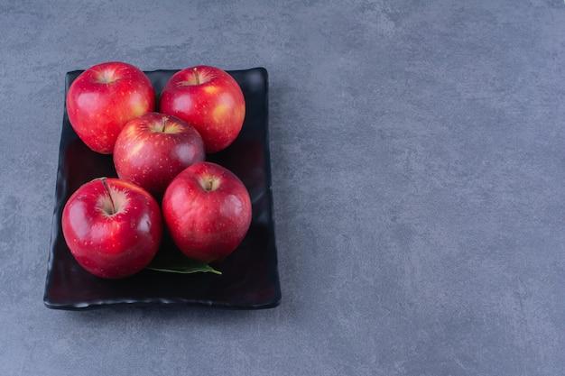 Manzanas rojas maduras en placa de madera sobre mesa de mármol.