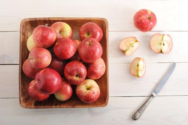 Manzanas rojas maduras en un plato sobre superficie de madera