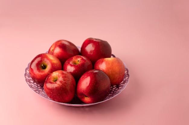 Manzanas rojas maduras red delicious, primer plano en una cesta en un rosa