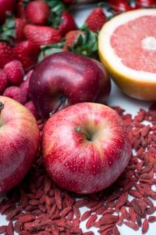 Manzanas rojas y otras frutas rojas y verduras sobre un fondo blanco
