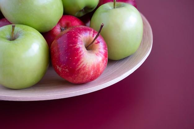 Manzanas rojas y verdes en una placa de bambú