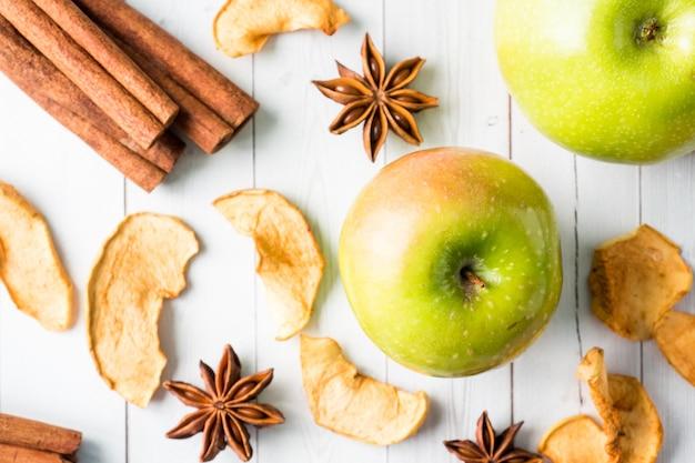 Manzanas secas manzanas verdes maduras palitos de canela anís estrellado sobre la mesa