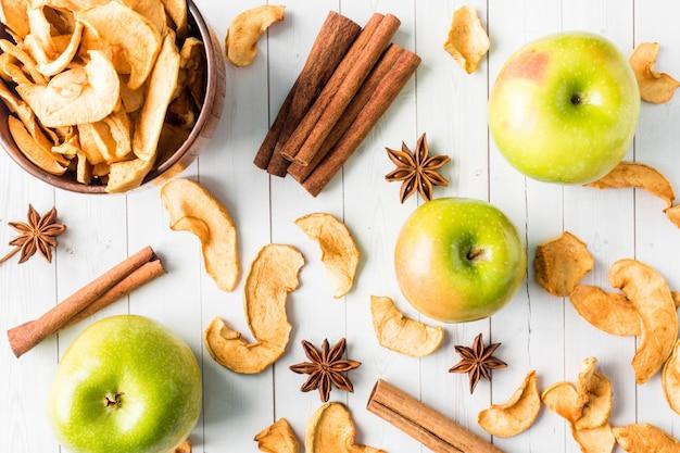 Manzanas secas en un tazón de madera manzanas verdes maduras en la mesa
