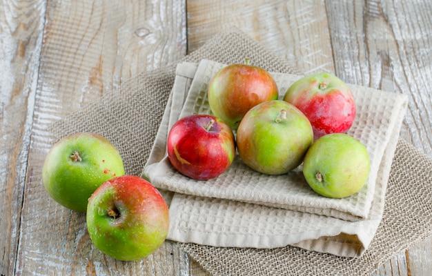 Manzanas sobre papel de cocina sobre madera y mantel individual. vista de ángulo alto.