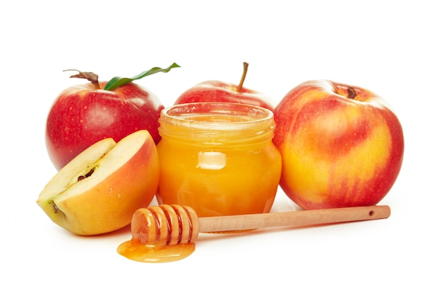 Manzanas y tarro de miel para vacaciones de año nuevo judío aislado en blanco
