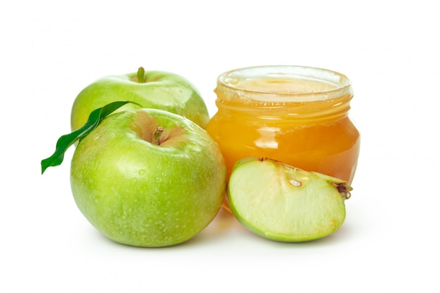 Manzanas y tarro de miel para vacaciones de año nuevo judío aislado sobre fondo blanco.