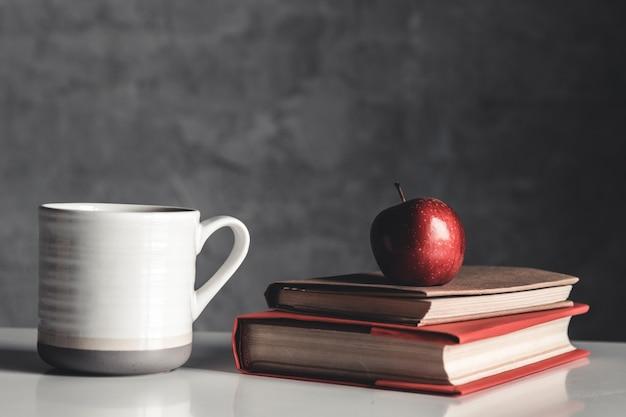 Manzanas, taza y libro sobre mesa blanca sobre fondo gris
