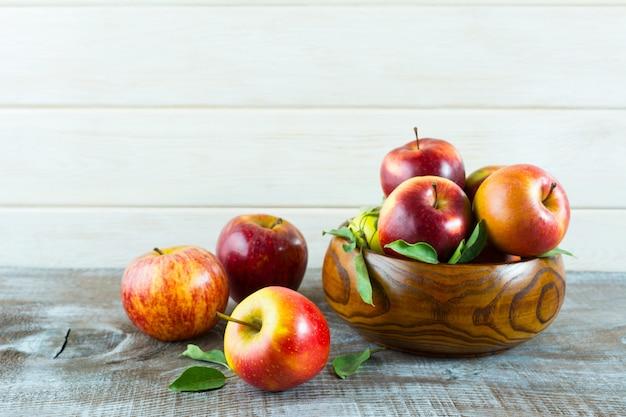 Manzanas en un tazón de madera en el fondo rústico