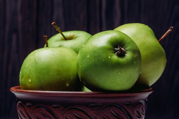 Manzanas en un tazón de verde maduro con gotas de rocío