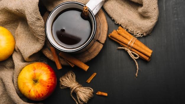 Manzanas y tela alrededor de la bebida especiada