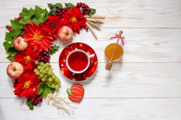 Manzanas, uvas, flores de dalia roja, sorbas rojas y miel con espacio de copia