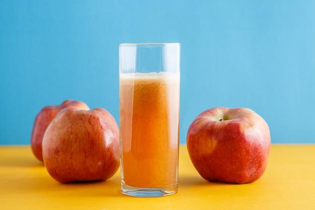 Manzanas y un vaso de jugo de manzana natural sobre fondo amarillo-azul