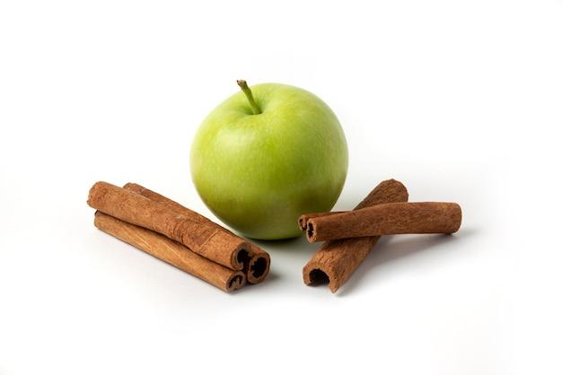Manzanas verdes y canela aislado en blanco