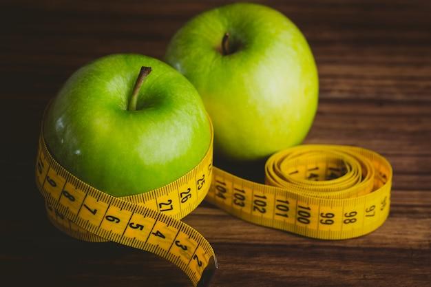 Manzanas verdes con cinta métrica.