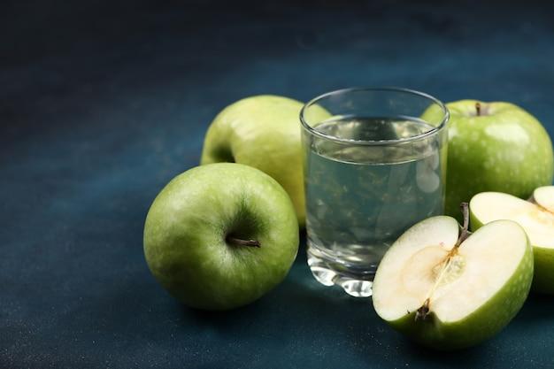 Las manzanas verdes enteras y medio cortadas con un vaso de jugo de manzana.