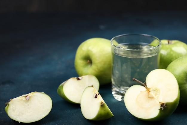 Manzanas verdes enteras y en rodajas con un vaso de jugo de manzana.