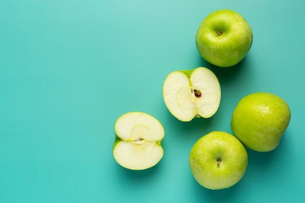 Manzanas verdes frescas cortadas por la mitad puestas sobre fondo verde claro