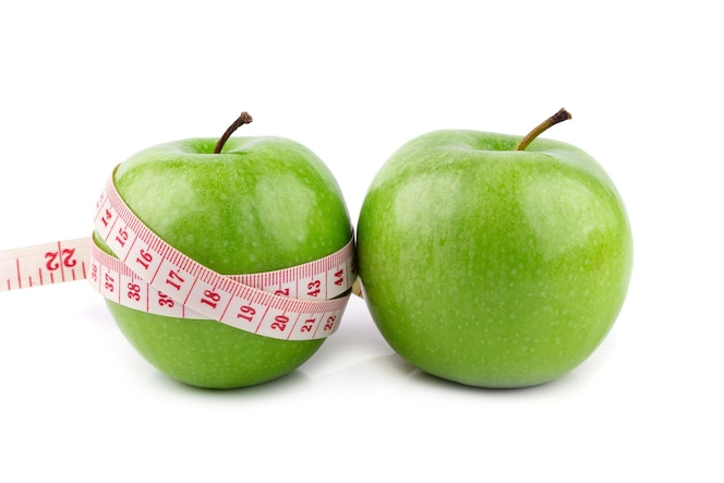Manzanas verdes frescas y cinta blanca que mide aislada en el fondo blanco.