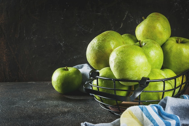 Manzanas verdes de granja orgánica cruda fresca en cesta de metal negro, oscuro oxidado, copyspace