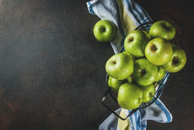 Manzanas verdes de granja orgánica cruda fresca en cesta de metal negro, oxidado oscuro, vista superior de copyspace
