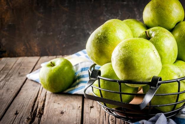 Manzanas verdes de granja orgánica cruda fresca en cesta de metal negro, viejo rústico de madera, copyspace