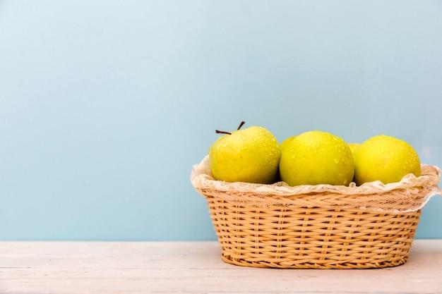 Manzanas verdes maduras jugosas frescas en cuenco en la tabla blanca de madera.