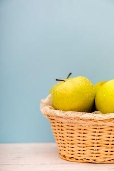 Manzanas verdes orgánicas en una cesta en una superficie de madera.
