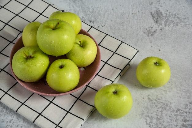 Manzanas verdes en un platillo de cerámica sobre la mesa