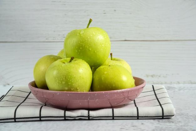 Manzanas verdes en un platillo de cerámica sobre la toalla