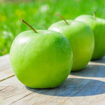Manzanas verdes recién cortadas en mesa de madera sobre hierba verde