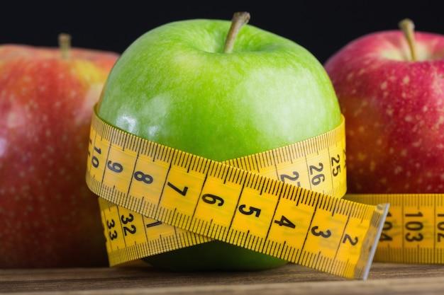 Manzanas verdes y rojas con cinta métrica