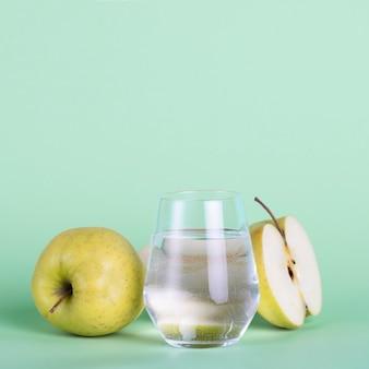 Manzanas verdes y vaso de agua sobre fondo verde