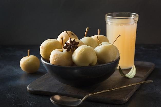 Manzanas en vinagre en un tazón y sidr de manzana en la mesa de piedra oscura.