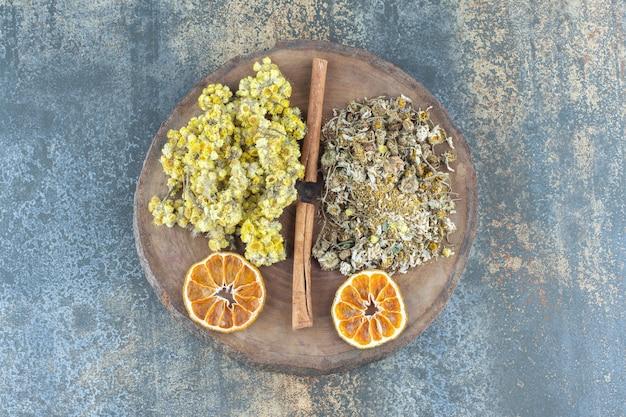 Manzanilla seca y crisantemo sobre pieza de madera.
