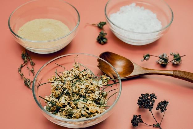 Manzanilla seca en un recipiente de vidrio sobre una superficie de sal marina y arcilla amarilla, polvo natural. crea cosméticos calmantes e hidratantes en un mortero en casa. una receta natural para el cuidado de la piel.