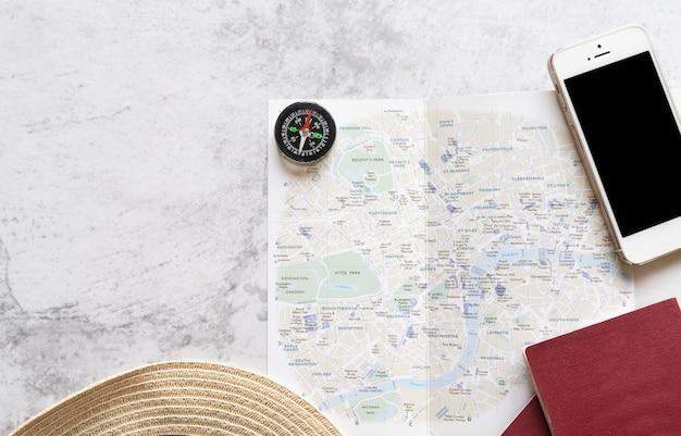 Mapa con accesorios de viaje sobre fondo de mármol.