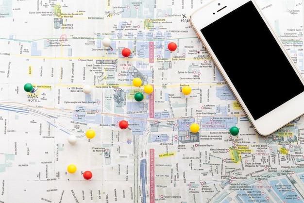 Mapa marcado con alfileres y un teléfono.