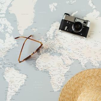 Mapa del mundo mínimo con alfileres, cámara retro, gafas de sol, sombrero de paja. planificación de viajes de vacaciones laicos planos