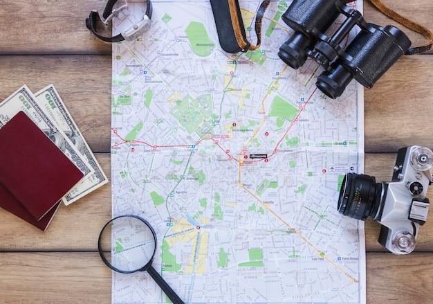 Mapa; pasaporte; billetes de banco lupa; cámara; prismáticos y reloj de pulsera sobre fondo de madera.
