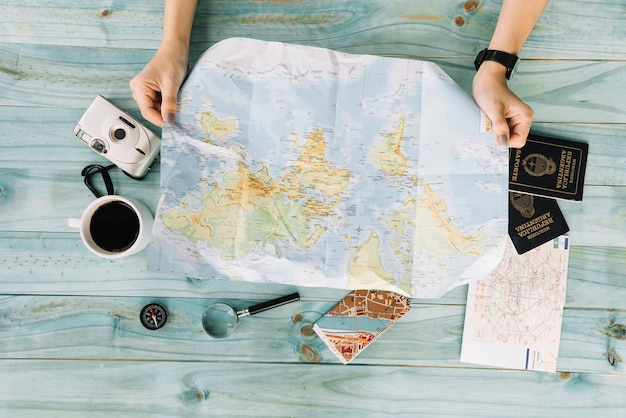 Mapa de tenencia de la mano femenina con cámara; café; lupa; mapa y pasaporte en tablón de madera