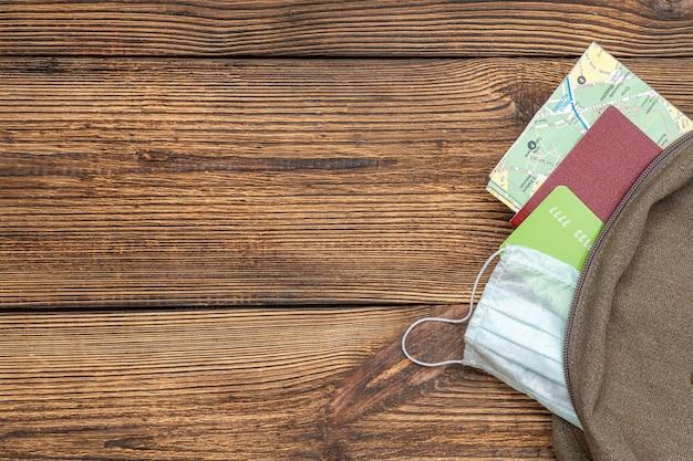 Mapa turístico, tarjeta de crédito, pasaporte, máscara protectora sobresale de la mochila de viaje en madera