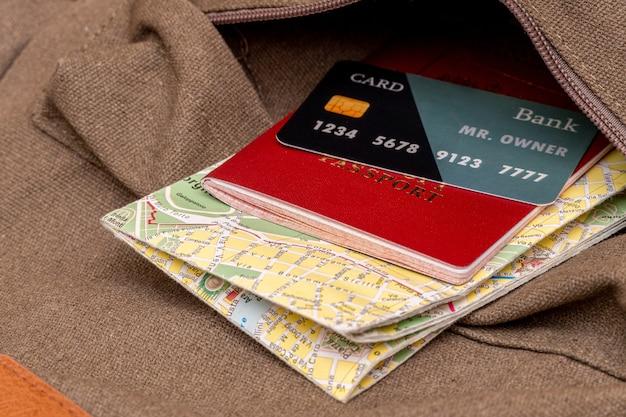 Mapa turístico, tarjeta, pasaporte en el bolsillo de la mochila de viaje.