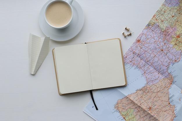 Mapa de viaje, diario y taza de café.