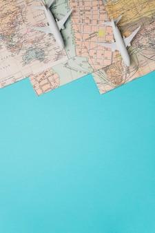 Mapas y aviones de juguete sobre fondo azul.