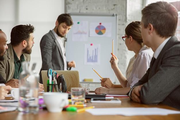 Mapas cerebrales. grupo de jóvenes empresarios que tienen una reunión. grupo diverso de compañeros de trabajo discuten nuevas decisiones, planes, resultados, estrategia. creatividad, lugar de trabajo, negocios, finanzas, trabajo en equipo.
