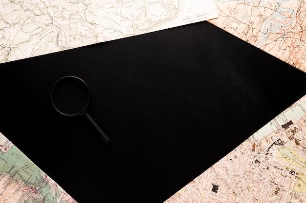 Mapas y lupa sobre escritorio negro.