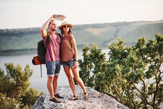 Los mapas no mienten, ese hombre ve aventuras por delante. pareja joven ha decidido pasar sus vacaciones de forma activa al borde de la hermosa roca con un lago al fondo.
