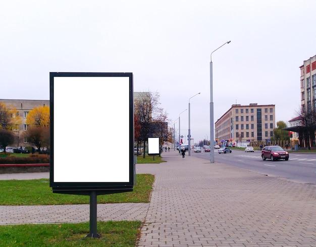 Maqueta en blanco de la cartelera del cartel de la calle vertical en el fondo de la ciudad